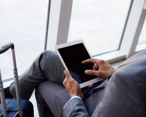 Businessman Using Digital Tablet In Airport Departure Lounge