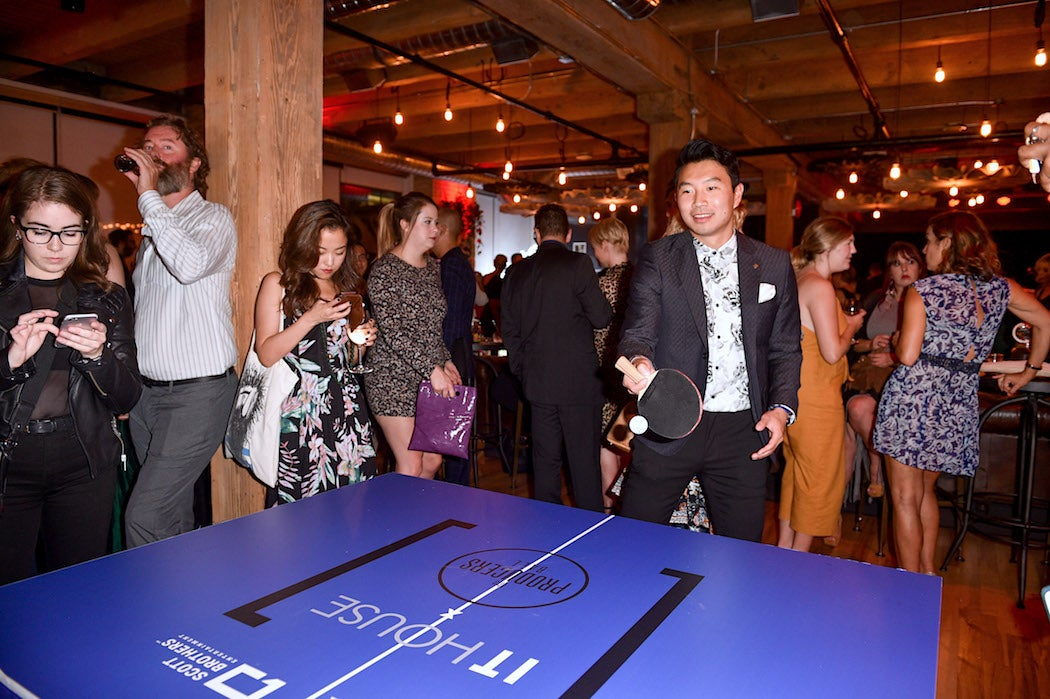 Simu Liu at the IT House Producers Ball TIFF 2018 Ping Pong Table | SWAGGER Magazine