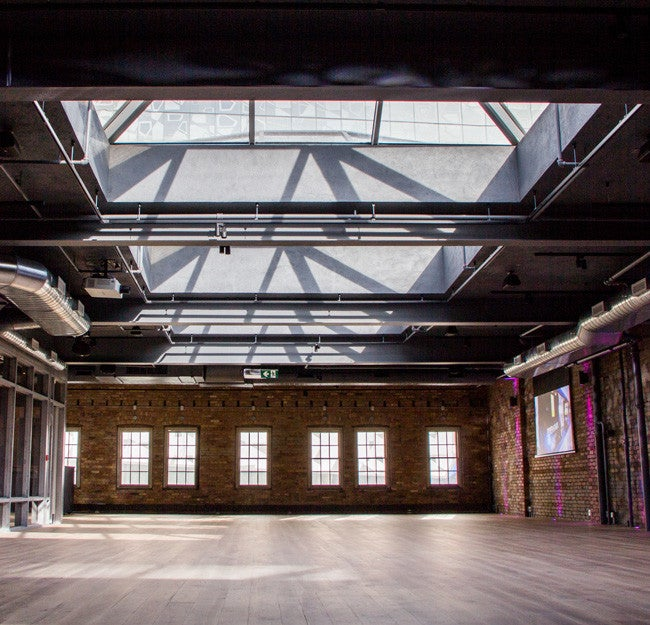 events space with skylight, brick walls and wood floors