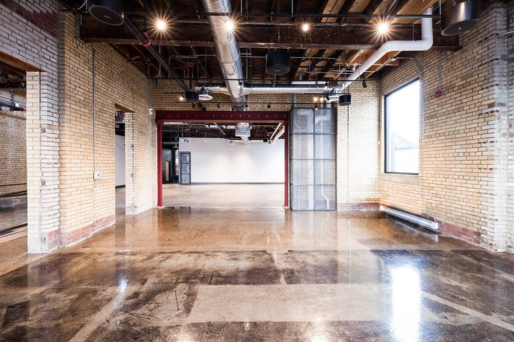 large event space with polished floors, brick walls, beams