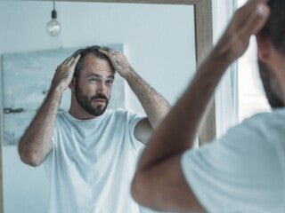 cropped shot of middle aged man with alopecia looking at mirror,