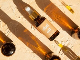 Cbd Oil Bottles And Droppers In Sunlight